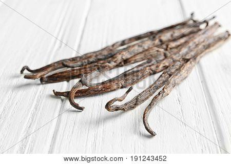 Dried vanilla sticks on light wooden background, closeup