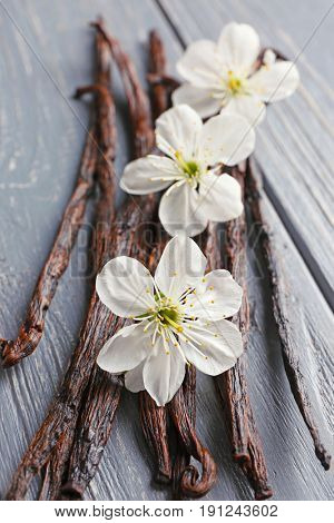 Dried vanilla sticks and flowers on wooden background, closeup