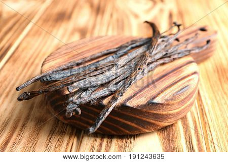 Board with dried vanilla sticks on wooden table, closeup