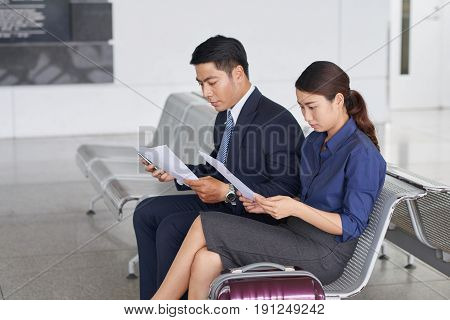 Portrait of two modern Asian  business people, man and woman, waiting for departure on business trip  in waiting zone of airport with big suitcases