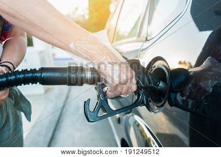 Woman fills gasoil into her car at a gas station. Woman wearing plastic gloves