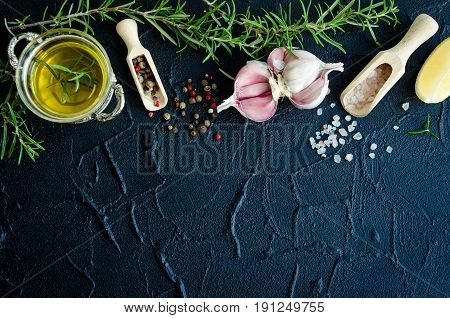 Herbs and spices selection - rosemary garlic lemon salt peppercorns and olive oil on dark stone table. Food flat lay. Creative layout with place for text. Copy space. Top view.