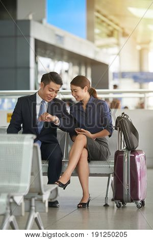 Portrait of smiling Asian man and woman checking time while waiting in airport departure zone travelling with suitcases