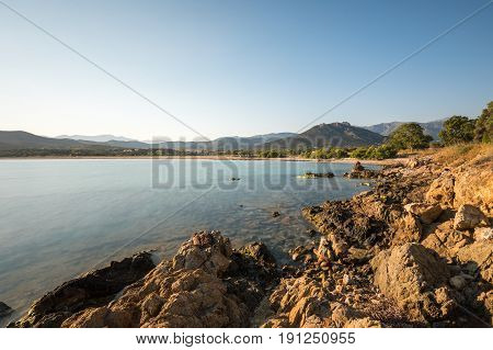 Still and clear Mediteranean water on the rocky coastline at Lozari in the balagne region of Corsica with beach trees and hills in the distance