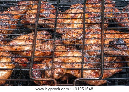 Grilled chicken legs and wings in metal spit on an open fire outdoor.
