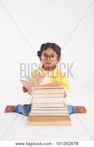 Full length portrait of adorable little girl sitting behind pile of books and reading encyclopedia, isolated on white background