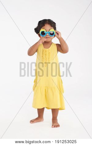 Full length portrait of cute little girl in yellow dress adjusting sunglasses and sucking lollipop, isolated on white background