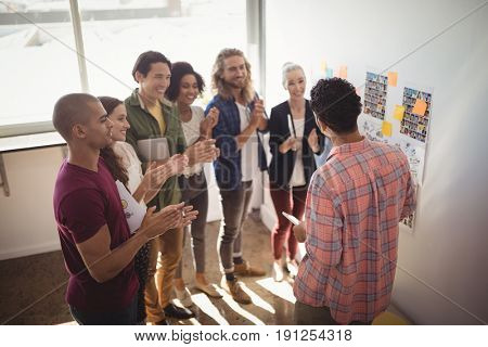 Team applauding while businessman discussing strategies at creative office