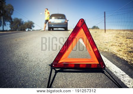 Emergency triangle in the road, with a man and his car in the background. Car breakdown scene.