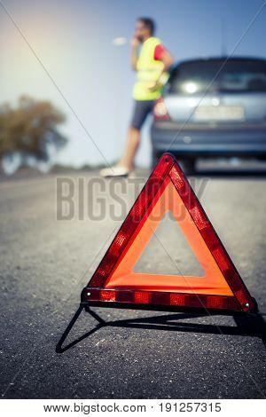 Reflective triangle for emergency. Car breakdown scene.