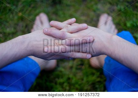 Caucasian man sitting on grass with crossed fingers on green background