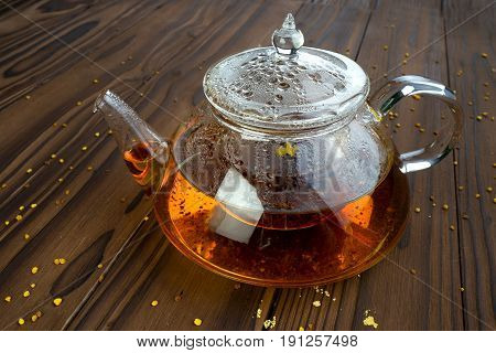 glass scalded teapot with tea on a brown table
