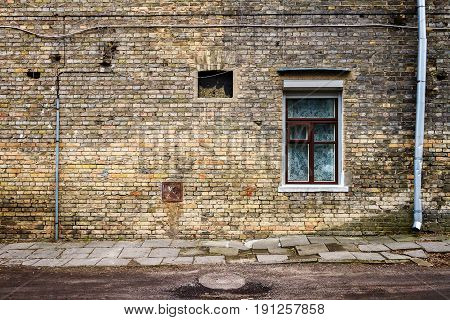 Aged weathered street wall with a windows. Architecture detail background. Old yellow brick wall