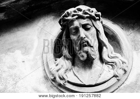 Face of Jesus Christ on old tombstone. Black and white image