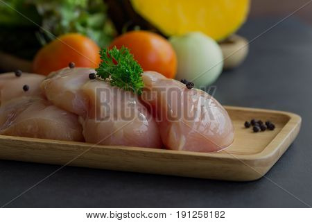 Chicken breast on wood plate sprinkle with black pepper and parsley. Slice raw chicken breast prepare for cooking with tomato pumpkin and onion. Raw chicken breast and vegetable on granite table. Raw chicken breast background.