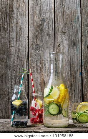 Citrus cucumber berries blueberry and raspberry sassy sassi water for detox in glass bottles with cocktail tubes on wooden background. Clean eating, healthy lifestyle concept, sunlight