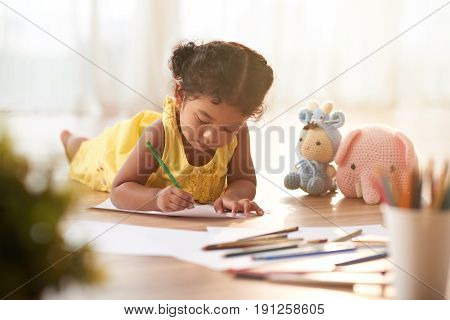 Concentrated toddler in yellow dress coloring picture with pencils while lying on floor, blurred background