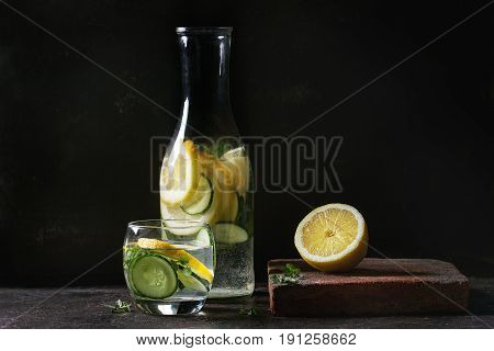 Citrus cucumber sassy sassi water for detox in glass bottle on dark black background. Clean eating, healthy lifestyle concept, sunlight