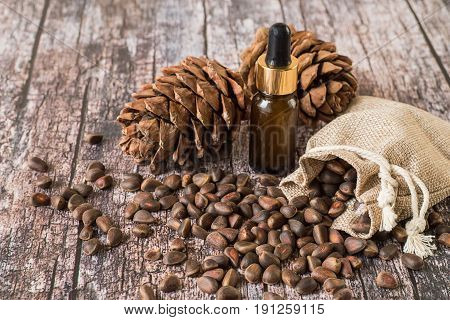 Cedar cones, a small sack with nuts and a bottle of oil on an old wooden background.