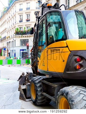 Yellow excavator on a construction site on city street