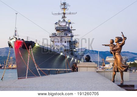 Novorossiysk Russia - July 2016: Monument to sailor's wife - mother and child. Warship Admiral Kutuzov. The area of Novorossiysk Sea Commercial Port.
