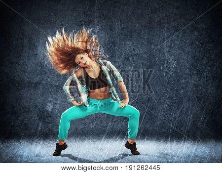 Young hip-hop dancer on grunge background