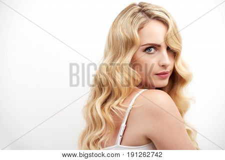 Portrait of beautiful young woman with  lush blond hair posing glancing at camera seductively against white background