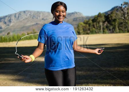 Fit woman skipping rope in the park on a sunny day