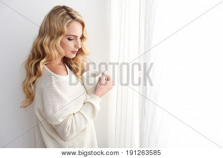 Portrait of beautiful blond young woman daydreaming standing by window at home wearing comfy white sweater and enjoying hot cocoa on winter day