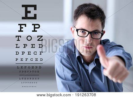 male face with spectacles on eyesight test chart background showing like hand eye examination ophthalmology concept