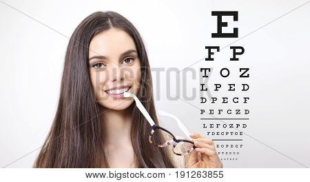 smile female face with spectacles on eyesight test chart background eye examination ophthalmology concept