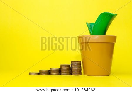 money coin stack growing and piggy bank or tree shaped money box on yellow background financial business saving money concept selective focus