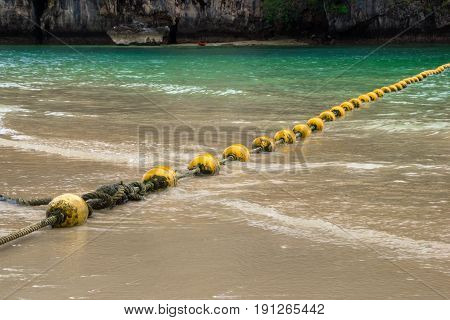 Travel To Krabi, Thailand. The Scenic View On The Sea With Yellow Buoys And A Rock From Phra Nang Be