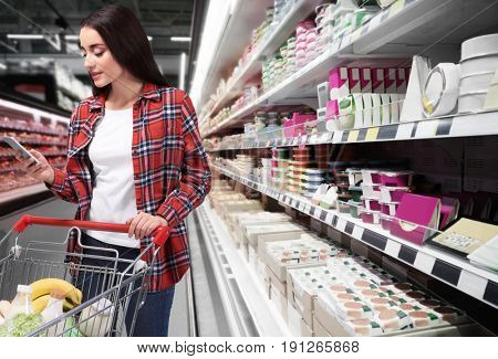 Young woman with market trolley checking shopping list on smartphone at supermarket