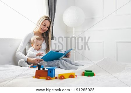 Child Education. Happy Mother With Her Toddler Sitting On The Bed And Reading A Book