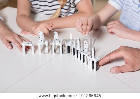 Family Sitting At Table And Playing With Domino Pieces, Cropped Image