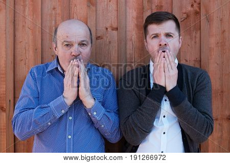 Two shocked man looking with surprise at camera. They close mouth with hands