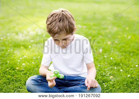 School kid playing with Tri Fidget Hand Spinner outdoors. Popular and trendy toy for hands for children and adults. boy having fun