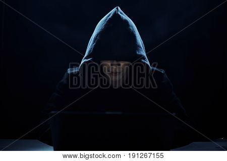 Programmer in a hood, a hacker on a dark background.