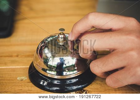 The woman's hands are pressing the bell to call for service.