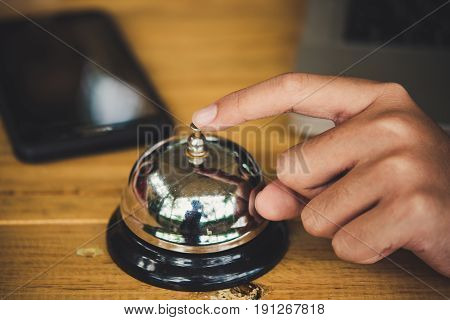 Hand of a woman using a bell