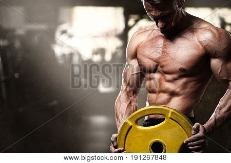 Middle aged bodybuilder posing in gym with weight in hands. Male fitness model with naked torso showing muscular and strong body