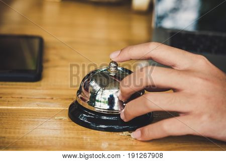 metallic hand-bell on a table hand press button