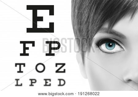 blue eyes close up on visual test chart eyesight and eye examination concept in white background