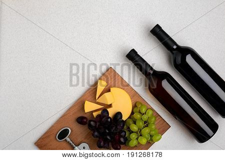 Two bottles of white and red wine, cheese and grapes. Top view with copy space