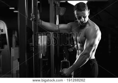 Strong muscular bodybuilder training on simulator, doing triceps exercise. Male fitness model posing in gym. Black and white image.