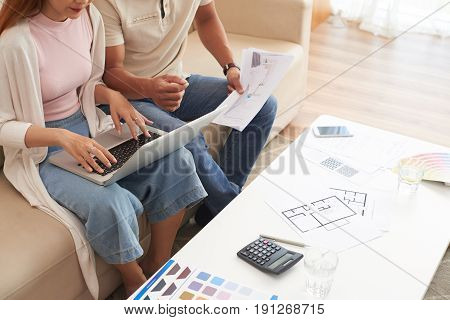 High angle shot of young couple discussing housing plans and using laptop