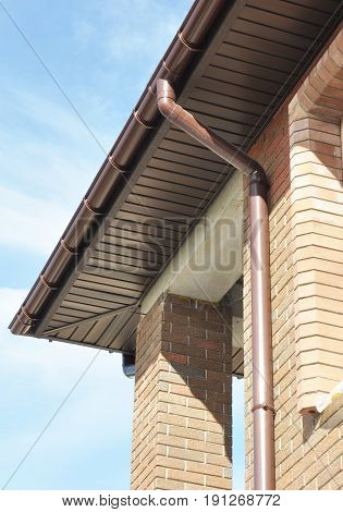 Rain Gutter Drain Pipe Downspout Installation on the Unfinished House Facade Brick Wall Outdoors. Install Roof Gutters System with Plastic Siding Soffits and Eaves.