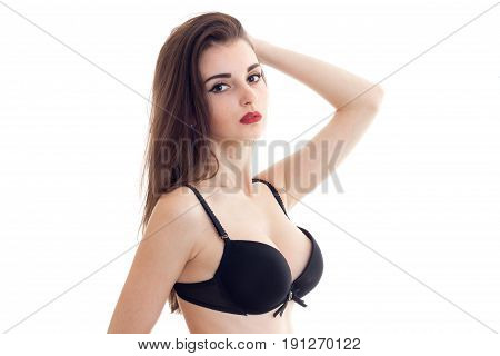 young brunette woman with red lips with big natural boobs in black bra looks at camera