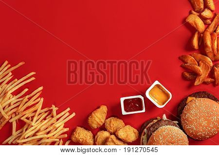 Fast food dish top view. Meat burger, potato chips and nuggets on red background. Takeaway composition. Wrapped French fries, hamburger, mayonnaise and ketchup sauces on red desk. Copy space
